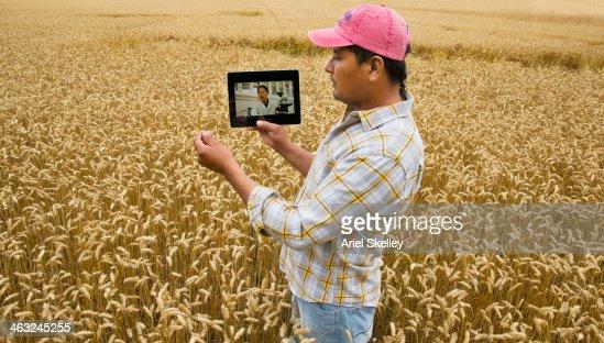 Hispanic farmer with digital tablet in crop field