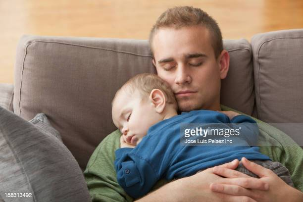Hispanic father and baby napping together