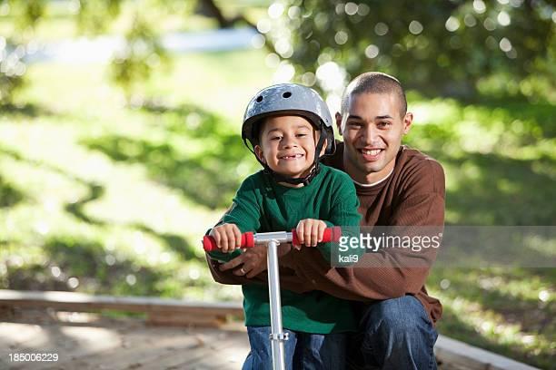 Hispanische Vater und Sohn auf einem Motorroller im park