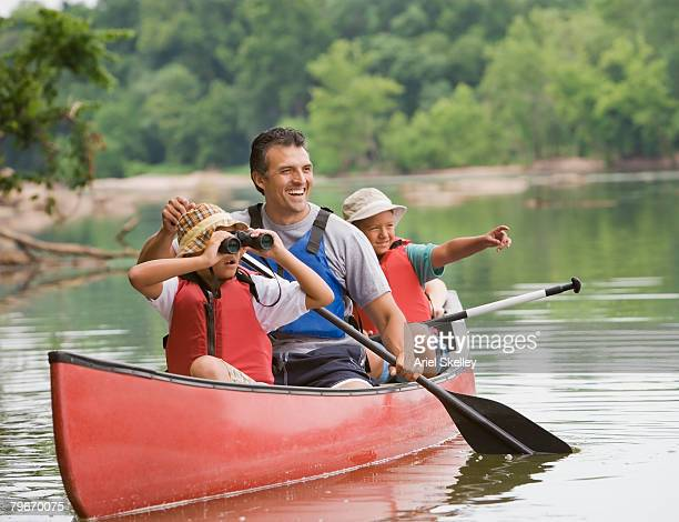 Hispanic father and children canoeing