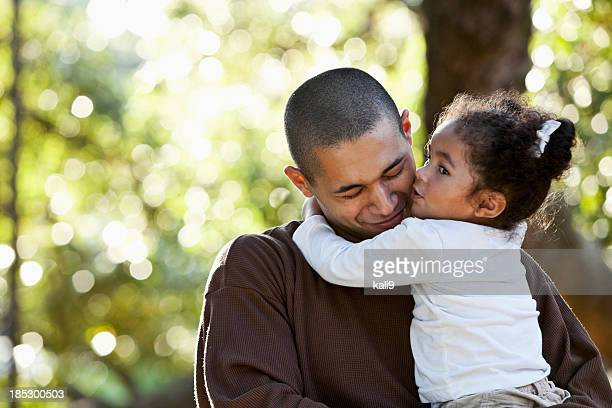 Hispanic father and daughter hugging at park