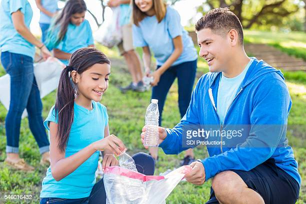 Hispanic father and daughter pick up trash in the park