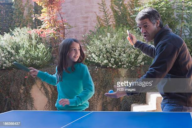 Hispanic father and daughter playing ping pong