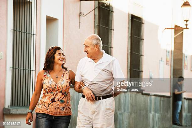 Hispanic father and daughter walking together in city
