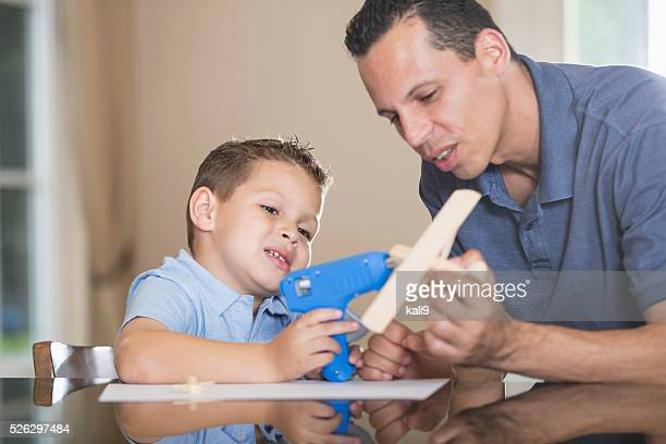 Hispanic father and son building wooden airplane model