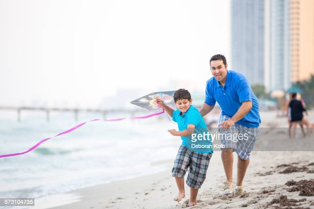 Hispanic father and son flying kite on beach