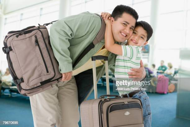 Hispanic father and son hugging at airport