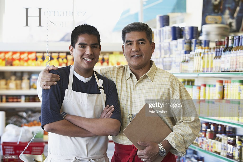 Hispanic father and son in family owned bodega : Stock Photo