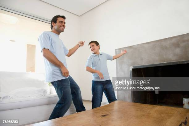 Hispanic father and son playing air guitar