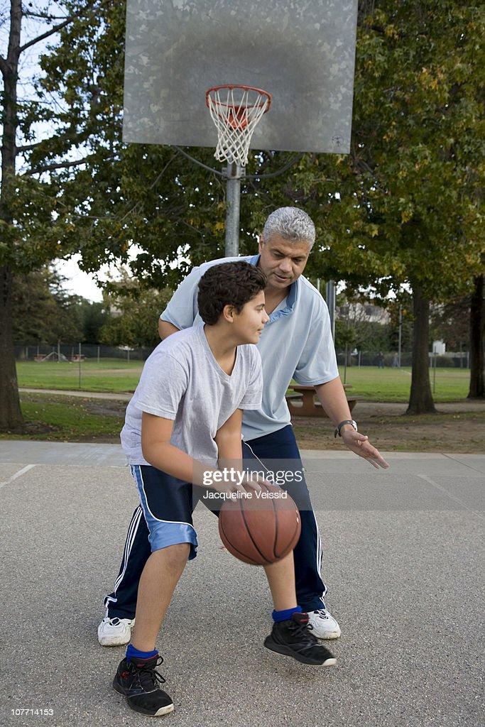 Hispanic father and son playing basketball : Stock Photo