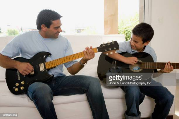 Hispanic father and son playing guitars