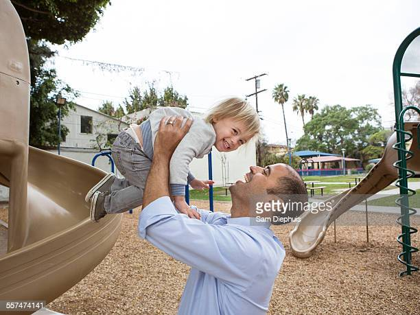 Hispanic father and son playing on playground