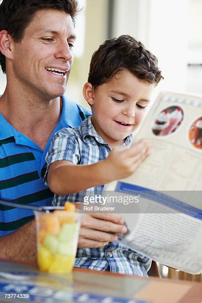 Hispanic father and son reading menu at restaurant