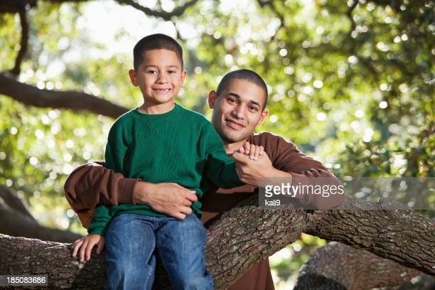 Hispanic father and son sitting in tree at park