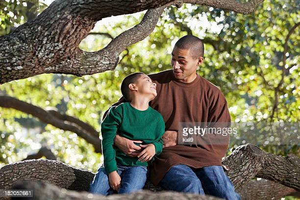 Hispanic father and son sitting in tree at park talking