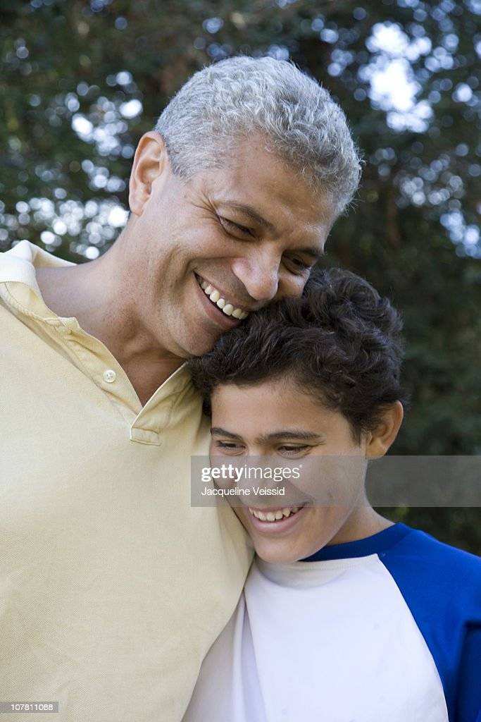 Hispanic father and son smiling : Stock Photo