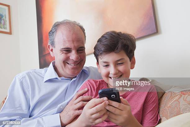 Hispanic father and son texting on cell phone