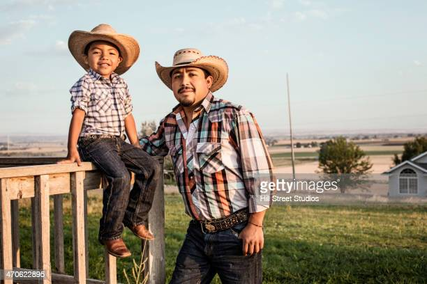 Hispanic father and son wearing cowboy hats outdoors