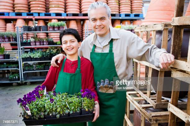 Hispanic father and son working at garden center