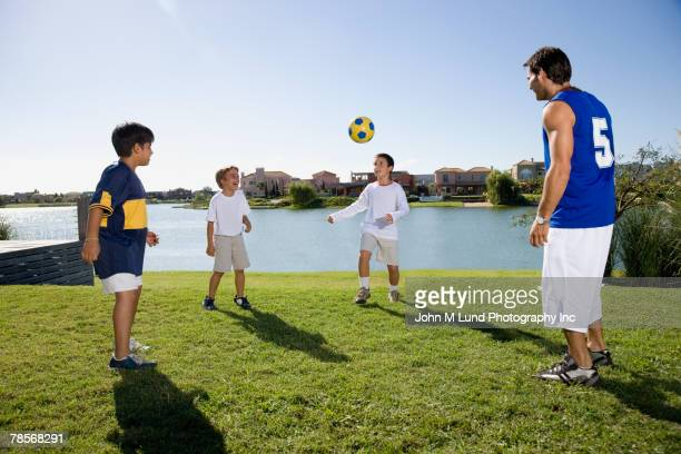 Hispanic father and sons playing with soccer ball