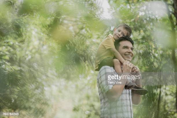 Hispanic father carrying son on shoulders in the woods