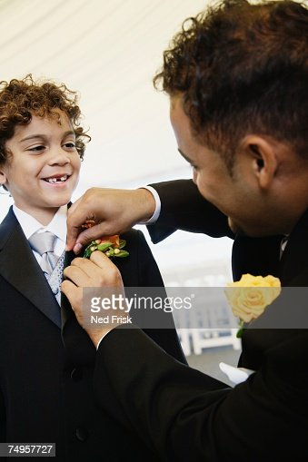 Hispanic father fastening boutonniere for son : Stock Photo
