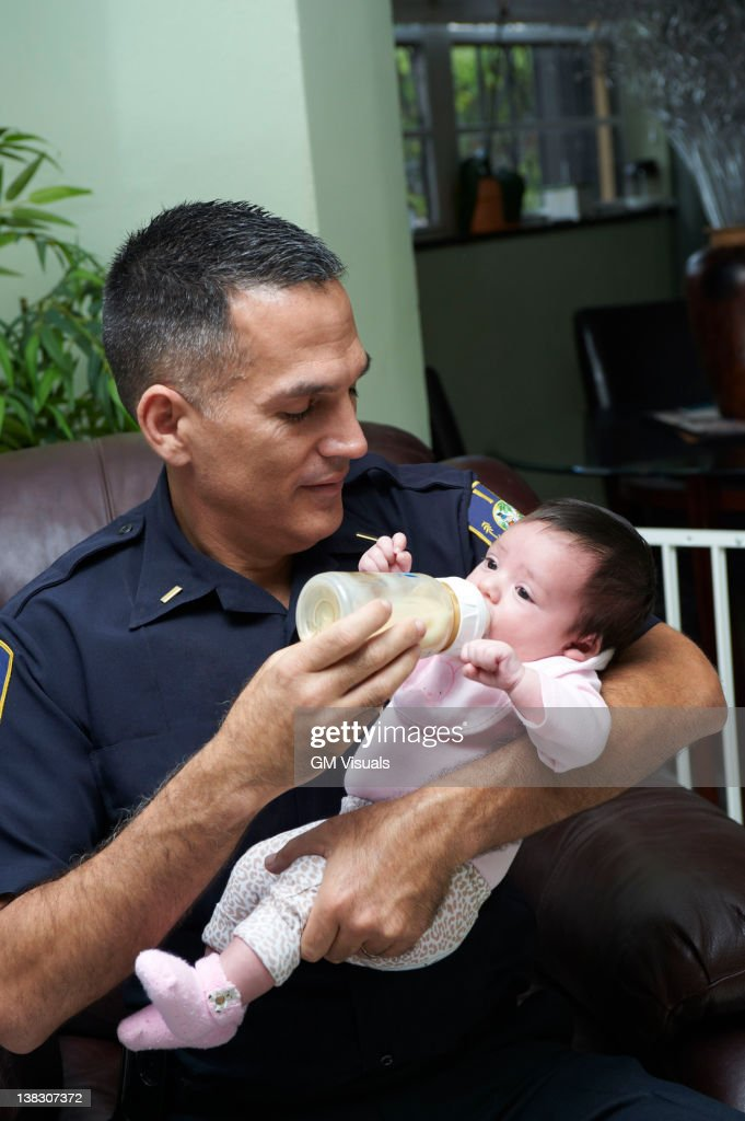Hispanic father feeding baby daughter : Stock Photo