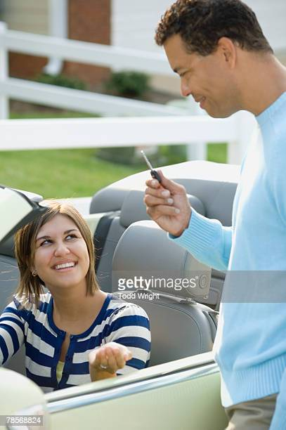 Hispanic father giving daughter car key
