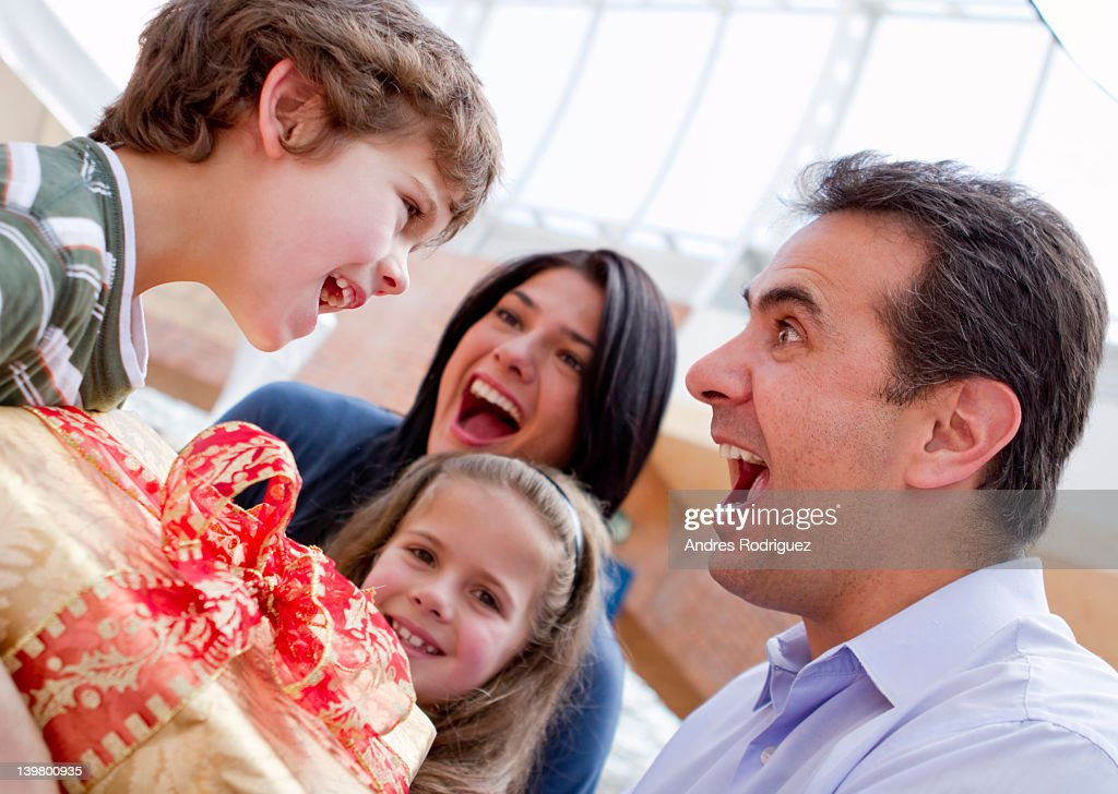 Hispanic father giving excited son birthday gift : Stock Photo