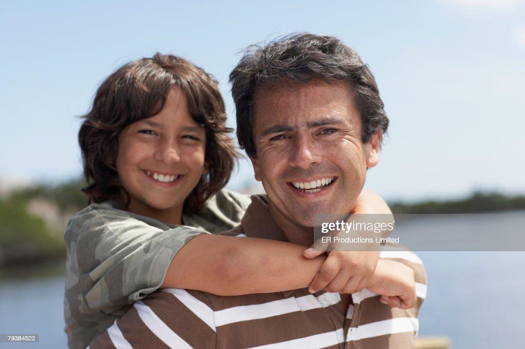 Hispanic father giving son piggyback ride : Stock Photo