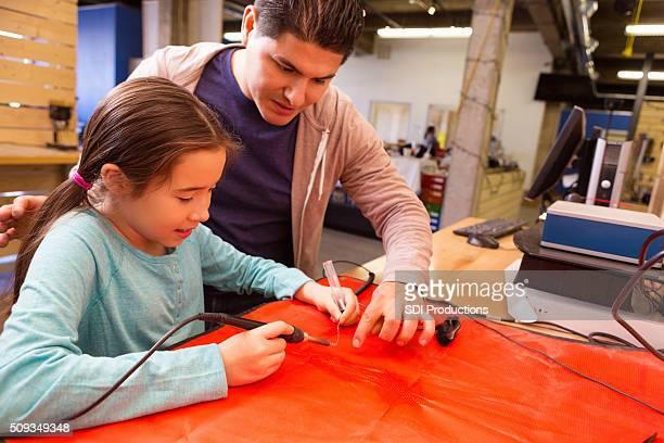 Hispanique père guides fille comme elle utilise soudure stylo