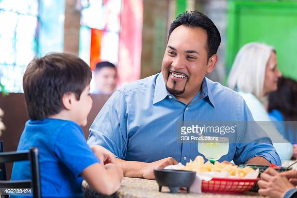 Hispanic father having meal in Tex-Mex restaurant with young son