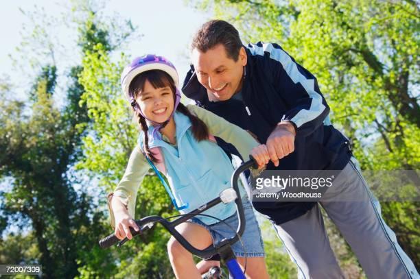 Hispanic father helping daughter ride bicycle