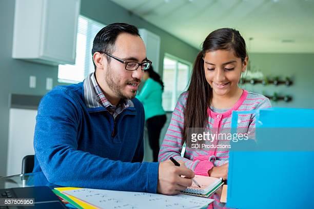 Hispanische Vater hilft Tochter bei Hausaufgaben