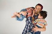 Hispanic father holding toddler children