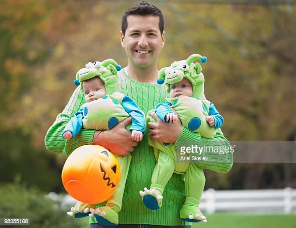 Hispanic father holding twin babies in Halloween costumes