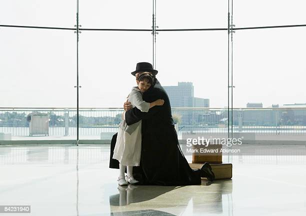 Hispanic father hugging daughter in airport