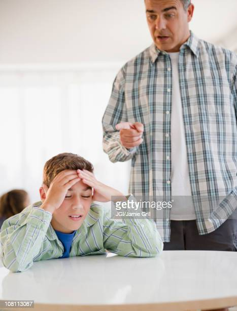 Hispanic father lecturing frustrated son