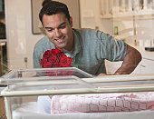 Hispanic father looking at newborn baby