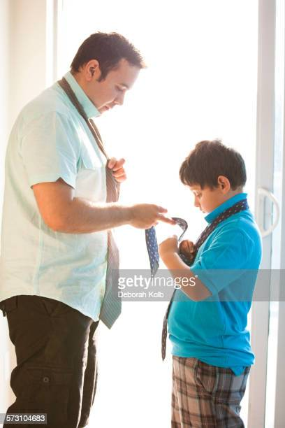 Hispanic father showing son how to tie necktie