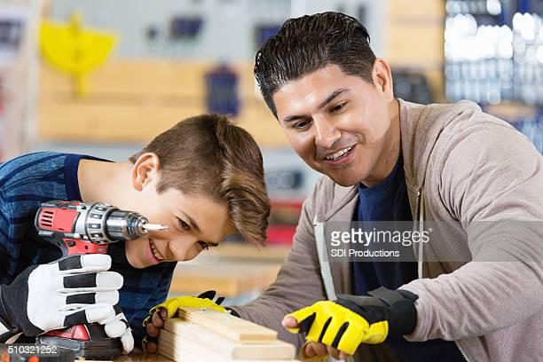 Preteen Ispanico padre insegna a suo figlio come esercizio del officina