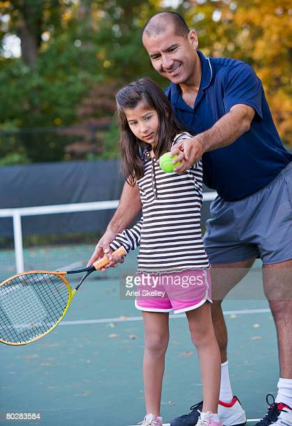 Hispanic father teaching daughter to play tennis