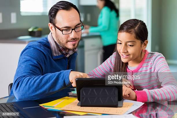 Hispanique père avec tablette pour aider sa fille à faire ses devoirs