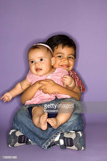 Hispanic female baby and male child portrait.