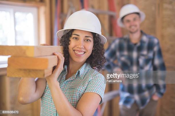 Hispanic female carrying a stack of 2x4's for DIY