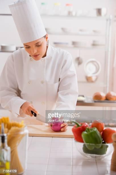 Hispanic female chef chopping onions