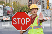 Hispanic female construction worker holding stop sign