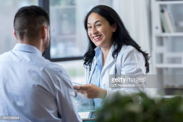 Hispanic female doctor discusses something with male patient