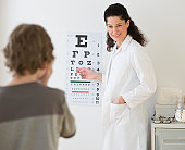 Hispanic female doctor pointing at eye chart for child