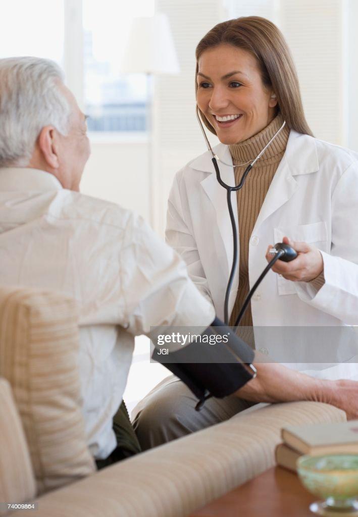 Hispanic female doctor taking patient's blood pressure : Stock Photo